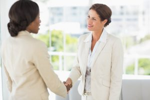 Two smiling businesswomen meeting and shaking hands in the office